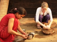 Rickshaw customer helping a Nepalese woman bake