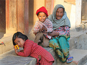 Woman and two children sitting on a wall