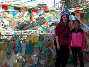 Jennifer standing by prayer flags in Tibet