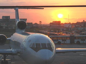 On the ground airplane with sun setting in the background