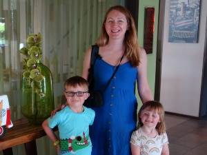woman standing with two children