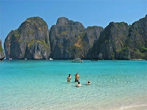 people in turquoise water at ko phi phi beach in thailand