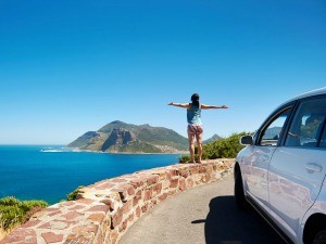Woman standing in front of the sea with a car in south africa