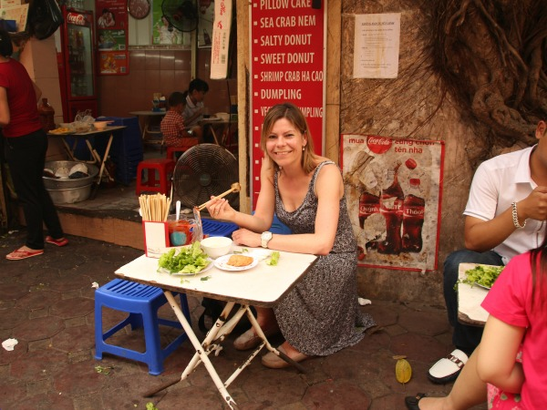 Woman sitting on a plastic stool in Hanoi