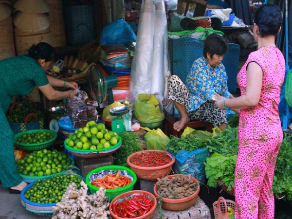 Locals selling food at market stall Vietnam