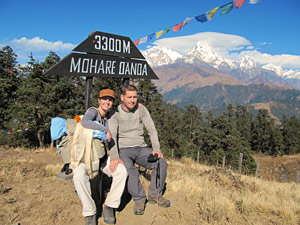 travellers sitting by trekking sign in nepal