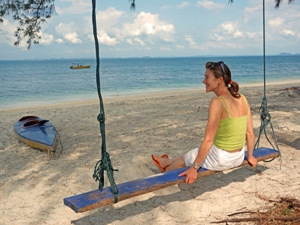 Woman on a swing on the beach