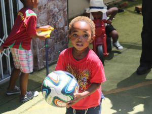 local child playing with ball in south africa