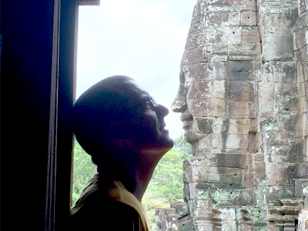 customer looking at stone face at angkor wat