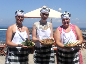 Cooking class team photo showing off Balinese dishes on the beach in Candidasa