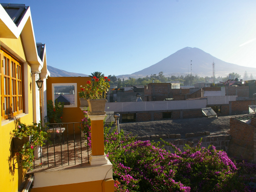 Peru yellow house with garden and mountain range in background