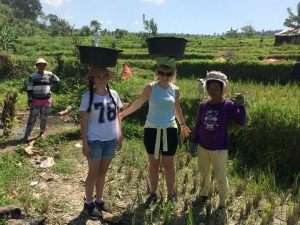 mother and daughter with local woman in rice paddies, ubud
