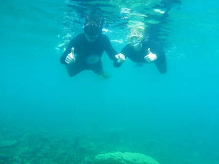 Two people snorkelling in tropical blue waters in asia
