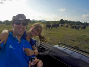 dad and daughter on a jeep safari with wild elephants in the background
