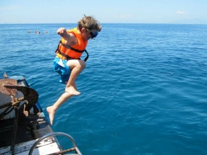 Boy jumping off boat