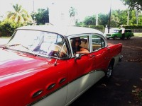 woman looking out of cuban classic car