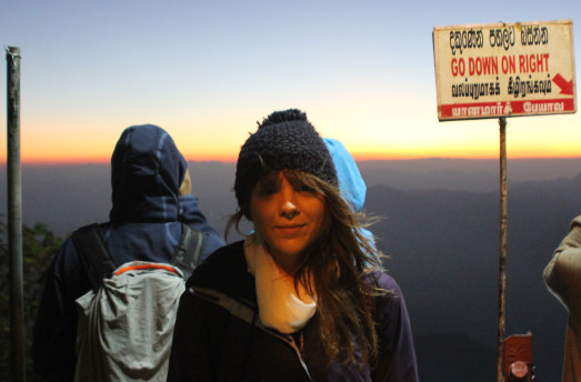 Woman stood at top of Adam's Peak in Sri Lanka with sunrise in background
