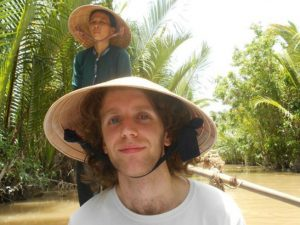 A man on a traditional Vietnamese boat on the Mekong Delta
