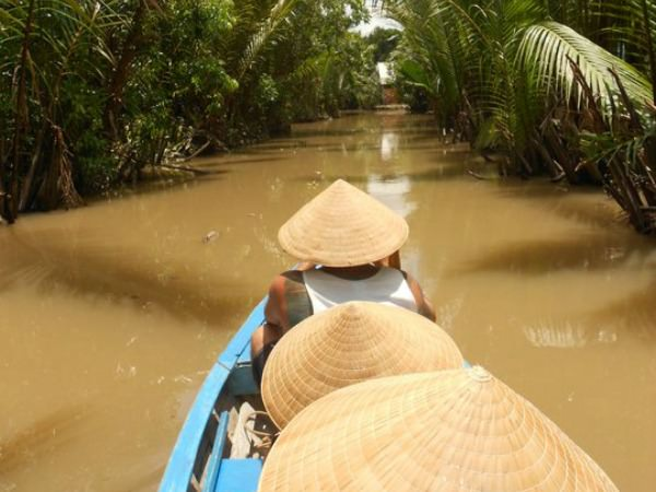 Boat trip along Mekong Delta while wearing traditional woven Vietnamese hats