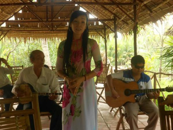 Vietnamese woman singing with an acoustic band at homestay on Mekong Delta