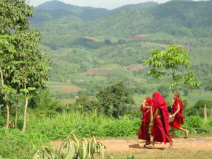 Green mountains with monks walking