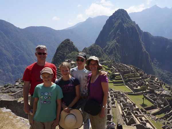 Family of five standing in front of Machu Piccuh sunny