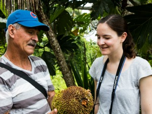 Network staff and local guide looking a Costa Rican fruit on Juanilama excursion
