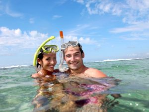 couple in sea with snorkeling gear on