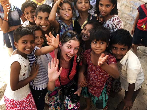 Women with local children in India waving at camera