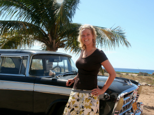 A woman standing next to a classic car next to a beach near Remedios in Cuba