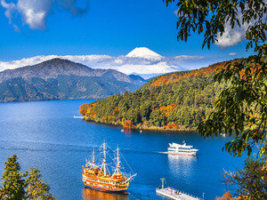Sightseeing ships floating along Lake Ashi with a majestic view of Mt Fuji in the background