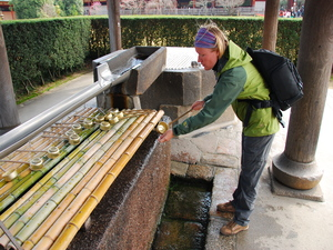Tourist leaning in to scoop a cup of holy water at a temple