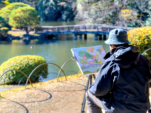 Local man sitting painting by lake