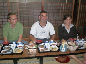 Man eating a traditional Japanese dinner with his friends at a table which is low to the ground