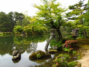A peaceful Japanese garden with a large pond in the middle, surrounded by lots of trees and greenery