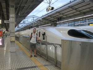A man standing beside a bullet train in Japan