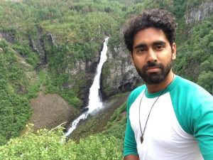 Man standing in front of a waterdfall wearing white and green t-shirt with greenery in background