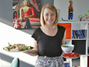 Product Manager Caroline in the office holding plates of food