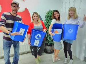 4 people holding up recycling bins and looking excited