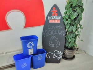 A sign reading Rickshaw Travel loves recycling