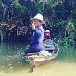 Thai fisherman smiling in fishing boat with prawn catch in his hand