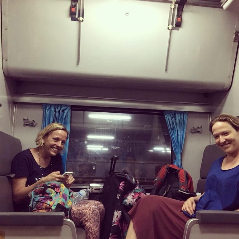 Two women sitting on a train opposite each other smiling with a window between them