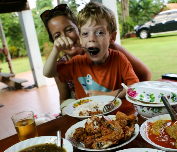 Young boy sitting on mum's lap eating food in Thailand
