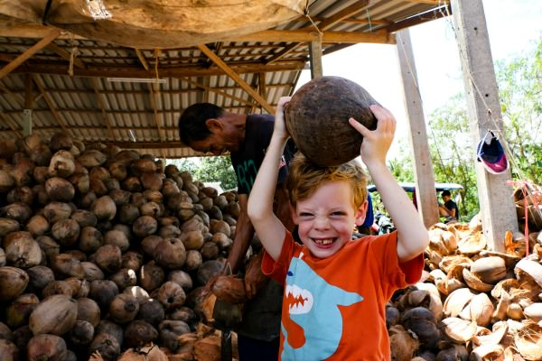 Young boy in Thailand with coconut held over his head