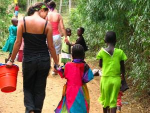 Young woman walking hand in hand with children in Kenya