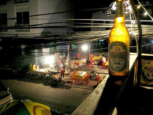 bottle of beerlao on ledge with street food restaurant in Laos