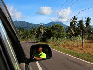 man driving car along road flores indonesia