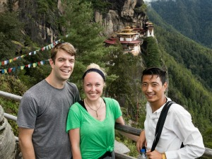 three people in bhutan smiling with tigers nest in the background