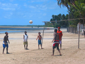 Local kids playing football on the beach Brazil