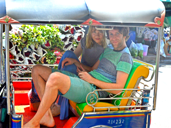 A couple in Thailand riding a Tuk-Tuk